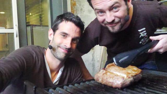 Zu sehen sind Philippe Gerber und Jann Hoffmann vor einem Grill. Auf dem Grill liegt ein ca. 1 kg schweres Stück Fleisch. Jann hat eine Grillzange in der Hand.