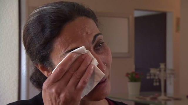 Frau wischt sich Tränen aus den Augen.