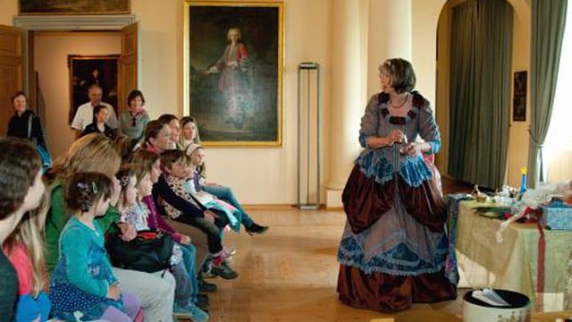 Kostümierte Frau im Museum Schloss Waldegg in Solothurn erklärt vor Kindern etwas.