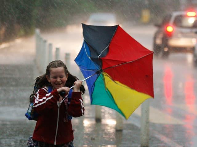 Ein Schulkind kämpft sich durch den strömenden Regen. Der Schirm wurde vom Wind umgestülpt.