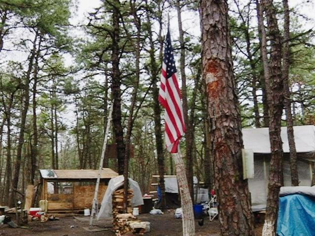 Improvisierte Baracke in einem Wald. An einem Baum hängt eine US-amerikanische Flagge