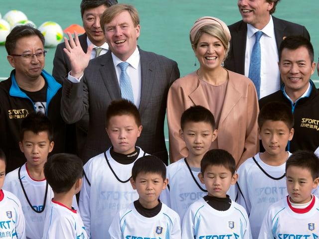 Máxima und Willem-Alexander bei einer Gruppenaufnahme mit chinesischen Kindern.