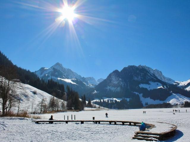 Der Himmel ist stahlblau über dem See. Personen tummeln sich auf dem gefrorenen See.