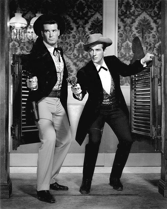 Zwei Western-Figuren stehen in einer Saloon-Türe und zücken je eine Pistole