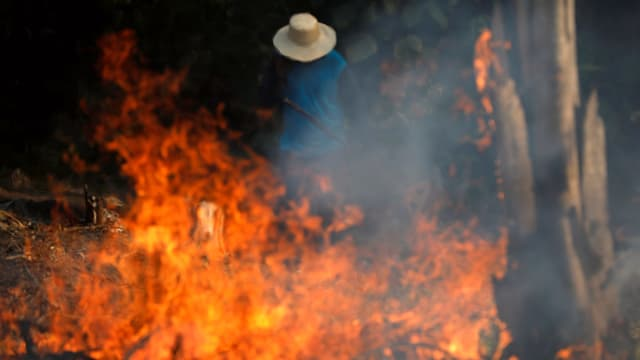 Ein Mann steht hinter einem Feuer.
