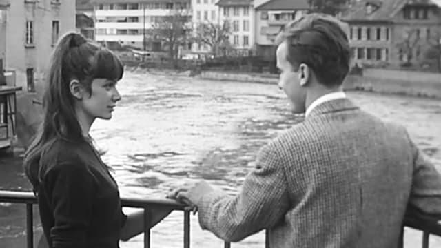 Junges Paar steht auf einer Brücke über der Aare; er hält ihre Hand.