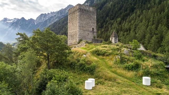 Ein Turm einer Burgruine, davor am Hang drei glänzende Heuballen.