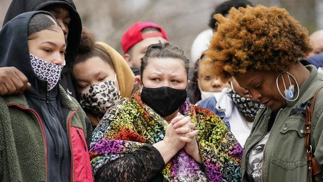 Mehrere Leute mit Masken, die weinen oder zu Boden blicken, umarmen sich und stützen sich aufeinander ab.