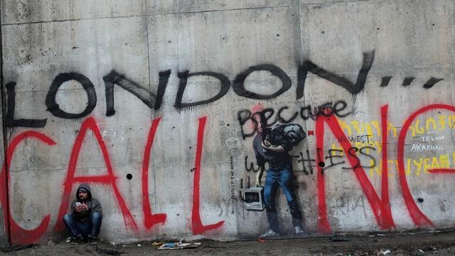 Mann sitzt vor Wand mit Grafitti «London Calling»