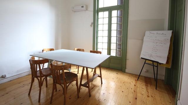 Ein Raum mit Parkettboden, einem kleinen Tisch und einer Flipchart.