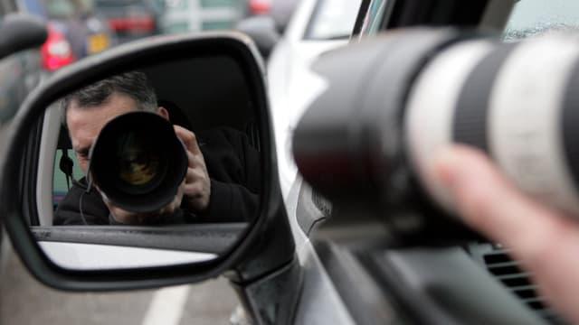 Das Spiegelbild eines Mannes mit Fotoapparat im Rückspiegel eines Autos.