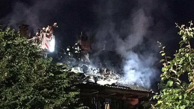 Ein Feuerwehrmann in einer Drehleiter über dem Haus