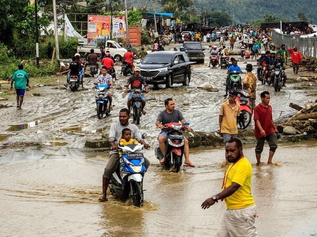 Einwohner der Stadt Sentani fahren auf Motorrädern durch fusshohe Wassermassen. Einige Anwohner laufen durch die Wassermassen.