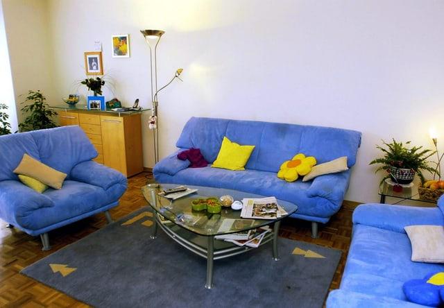 Wohnzimmer mit drei blauen Sofas, einem Teppich und einem Salontisch.