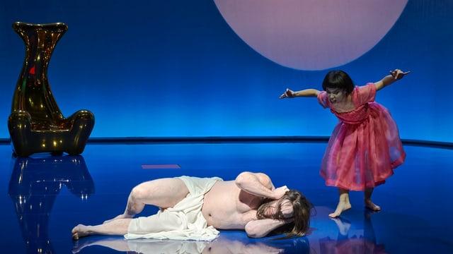 Eine Frau in einem Kleid schreit einen am Boden liegenden, nur in Laken gekleideten Mann an, der sich die Ohren zuhält.