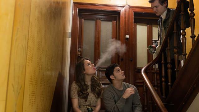 Eine junge Frau und ein junger Mann sitzen auf der Treppe eines Treppenhauses. Ihnen kommt ein junger Mann entgegen.