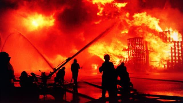 Personen vor einem riesigen Feuer.