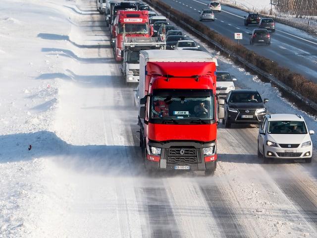 Wetterbedingter Stau auf verschneiter Autobahn.