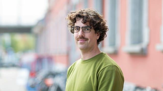 ein junger Mann mit Brille und grünem Pullover