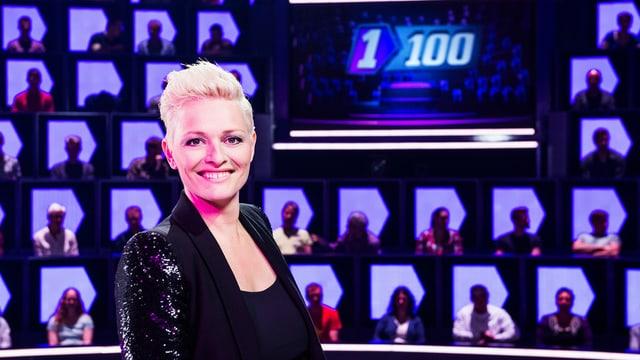 Susanne Kunz steht vor dem 1 gegen 100 Studiodekor in welchem einige Kandidaten und Kandidatinnen zu sehen sind.