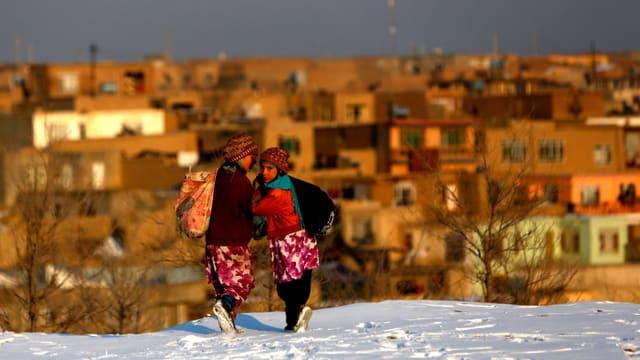 Zwei afghanische Mädchen gehen über den Schnee.