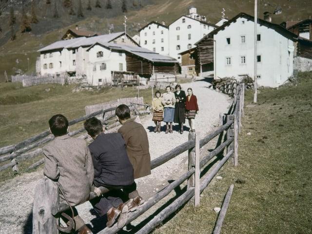 Bild aus den 50er Jahren. Drei Männer beobachten vier vorbeilaufende Frauen in einem Bergdorf.