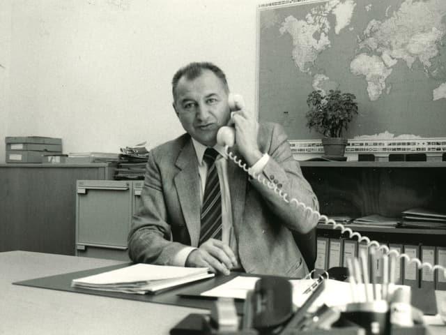 Schwarz-Weiss-Fotografie mit dem Reiseberater, der während eines Telefongesprächs hinter seinem Schreibtisch sitzt.