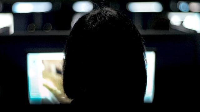 Eine Frau sitzt vor einem Computerbildschirm.
