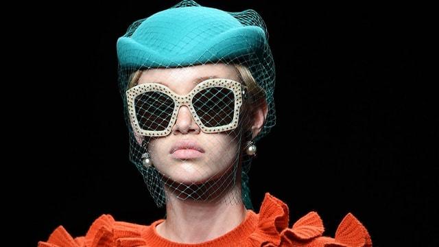 Ein Model mit Hut und Sonnenbrille.