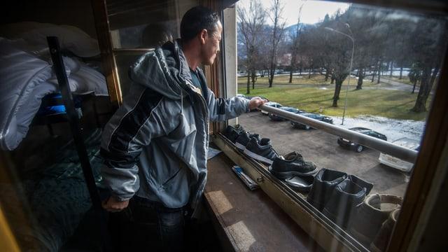 Ein Mann in einem Asylheim schaut zum Fenster hinaus.
