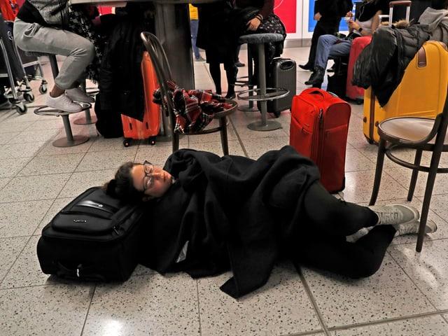 Eine Frau liegt am Boden auf ihrem Koffer.