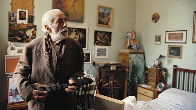 Ein alter Mann mit Gitarre in seinem Altersheim Zimmer.