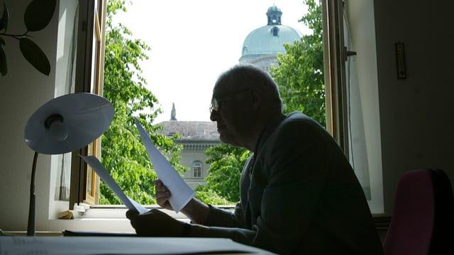 Mann in einem Büro mit Aussicht auf das Bundeshaus