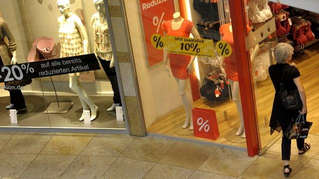 Eine Person betritt einen Kleiderladen