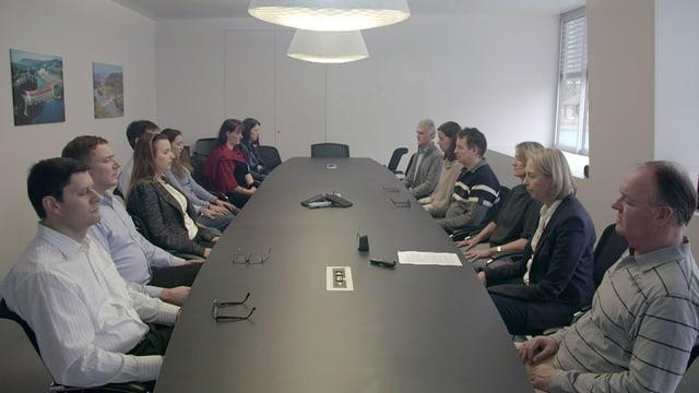 Rund ein Duzend Menschen sitzen mit geschlossenen Augen um einen ovalen Tisch.