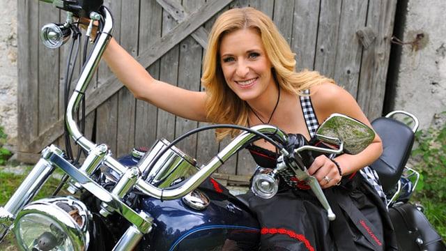 Hertel in rockig-angehauchtem Dirndl auf Harley Davidson.