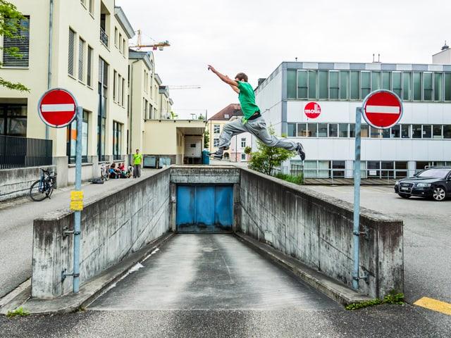Ein Mann springt über eine Einfahrt zu einem Parkhaus