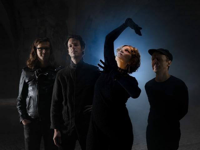 Drei Männer stehen im Hintergrund. Es ist sehr dunkel. Eine Frau steht vorne und streckt ihre Arme nach oben.