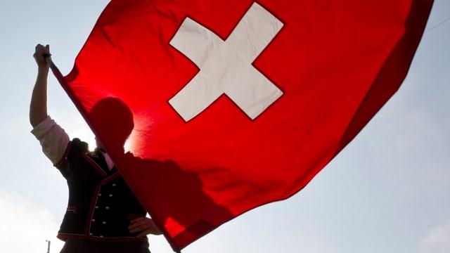 Ein Schwinger hält die Schweizer Fahne, die im Wind flattert-