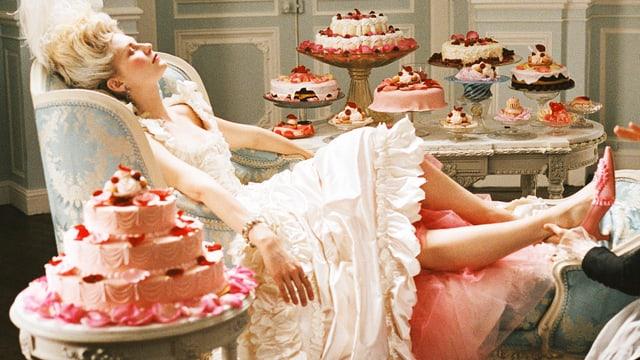 Marie-Antoinette liegt auf einem Sessel. Sie ist von Torten umringt.