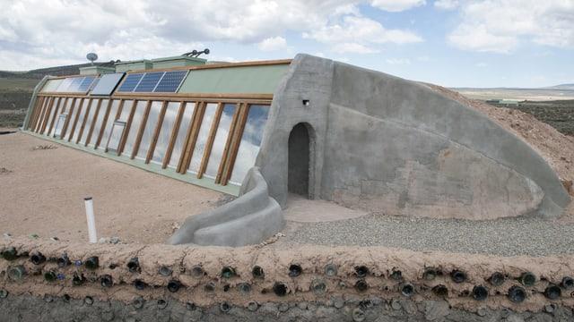 Grünliches, in den Boden gebautes Haus mit grossen Fensterfront und Solarzellen auf dem Dach