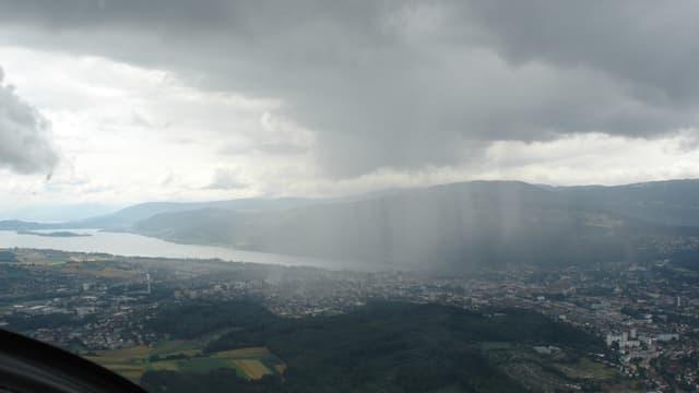 Flugbild: Landschaft mit See und Jurahügeln im Hintergrund. Im Vordergrund graue Wolke mit fallenden Regenstreifen.