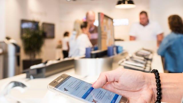 Eine Frau schaut sich ein Handy an in einem Laden.