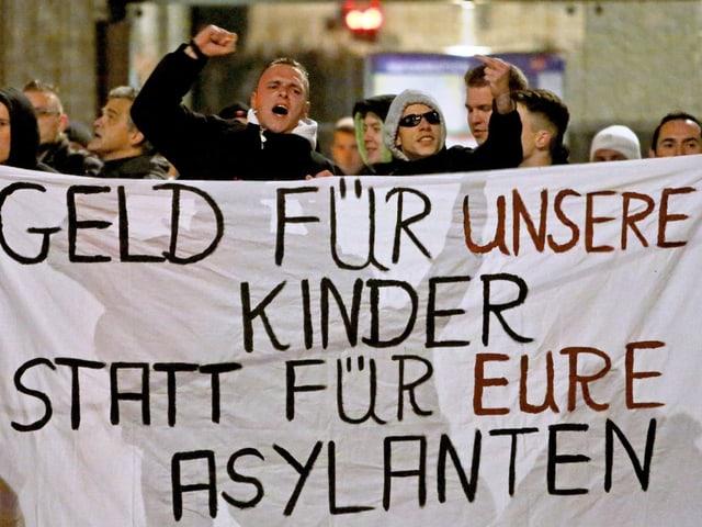 """Anhänger der """"Patriotischen Europäer gegen die Islamisierung des Abendlandes"""" in Leipzig tragen ein Transparent an einem Protestmarsch am 2. November 2015. Die Aufschrift lautet: """"Geld für unsere Kinder statt für Eure Asylanten""""."""
