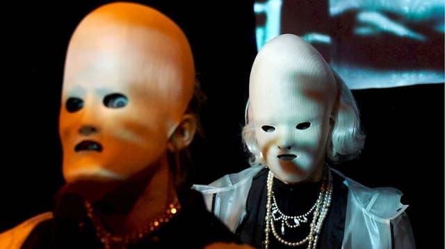 Zwei Menschen mit eierförmigen Masken.