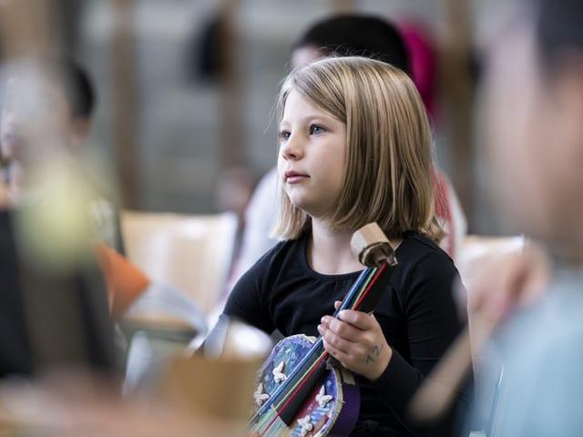 Ein kleines Mädchen hält eine selbstgebastelte Geige in der Hand und hört dem Lehrer zu.