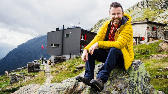 Nik Hartmann sitzt auf einem Stein, im Hintergrund ist eine Hütte zu sehen.