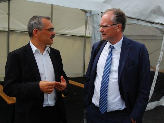 Zwei Staatsräte im Gespräch vor einem Zelt.