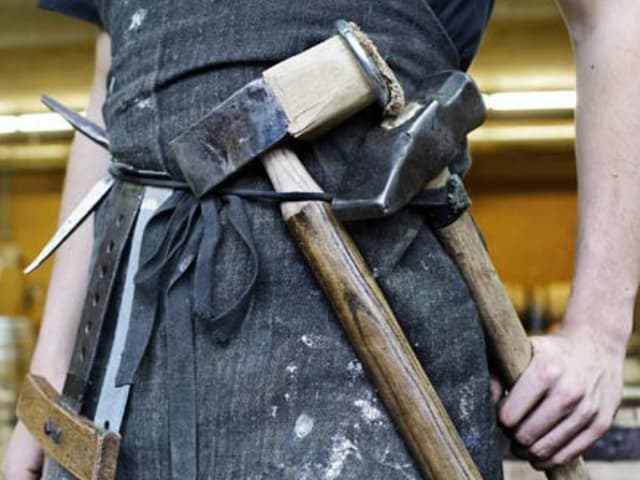 Bildausschnitt: Am Gürtel einer Arbeitsschürze hängen schwere Hämmer und Metallwerkzeuge.