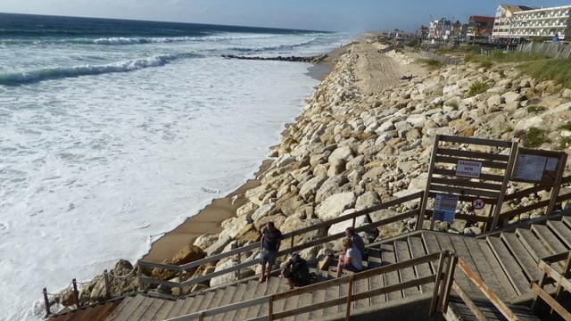 Ein Deich an einem Strand, der Ozean kommt immer näher